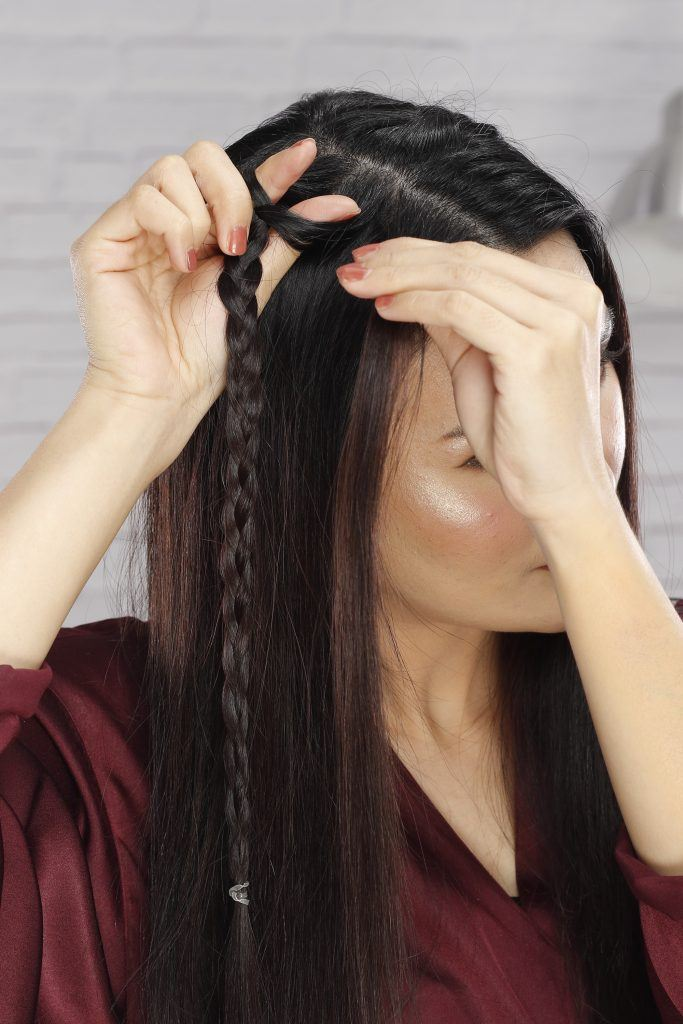 how to braid long hair: Girl is creating a gap on her hair and pulls a section of hair through it