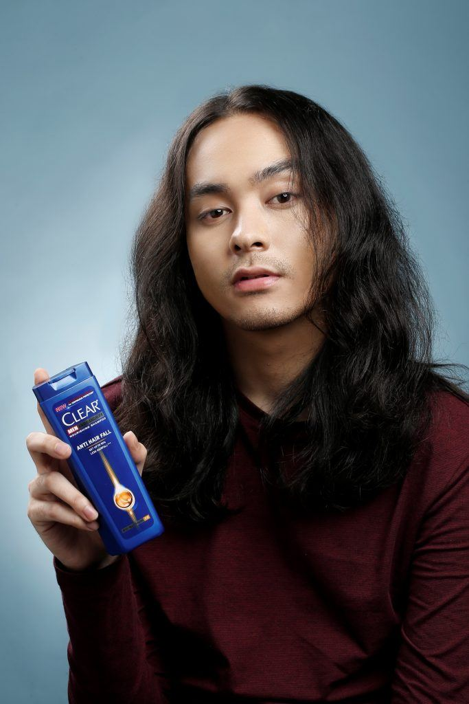 Asian man with long hair holding a CLEAR shampoo