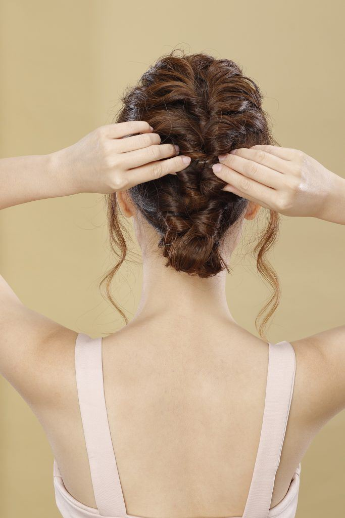 Girl's back view is seen as she pulls sections of her to volumize it