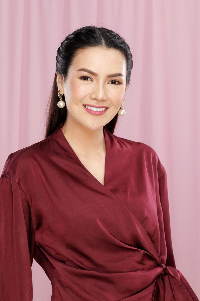 Asian woman with a braided half updo wearing a red blouse