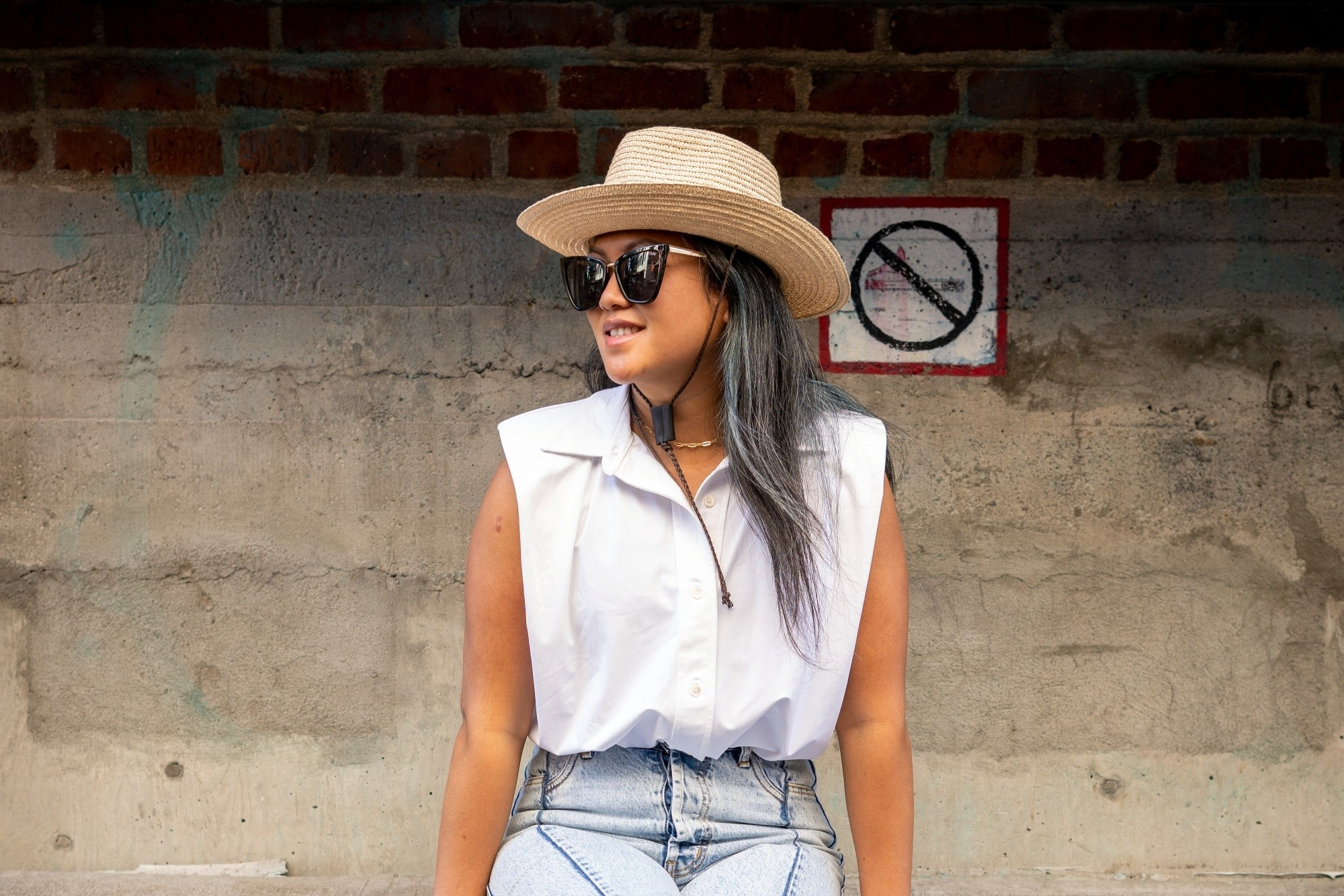 Asian woman with ash gray hair for morena skin wearing a hat and white top