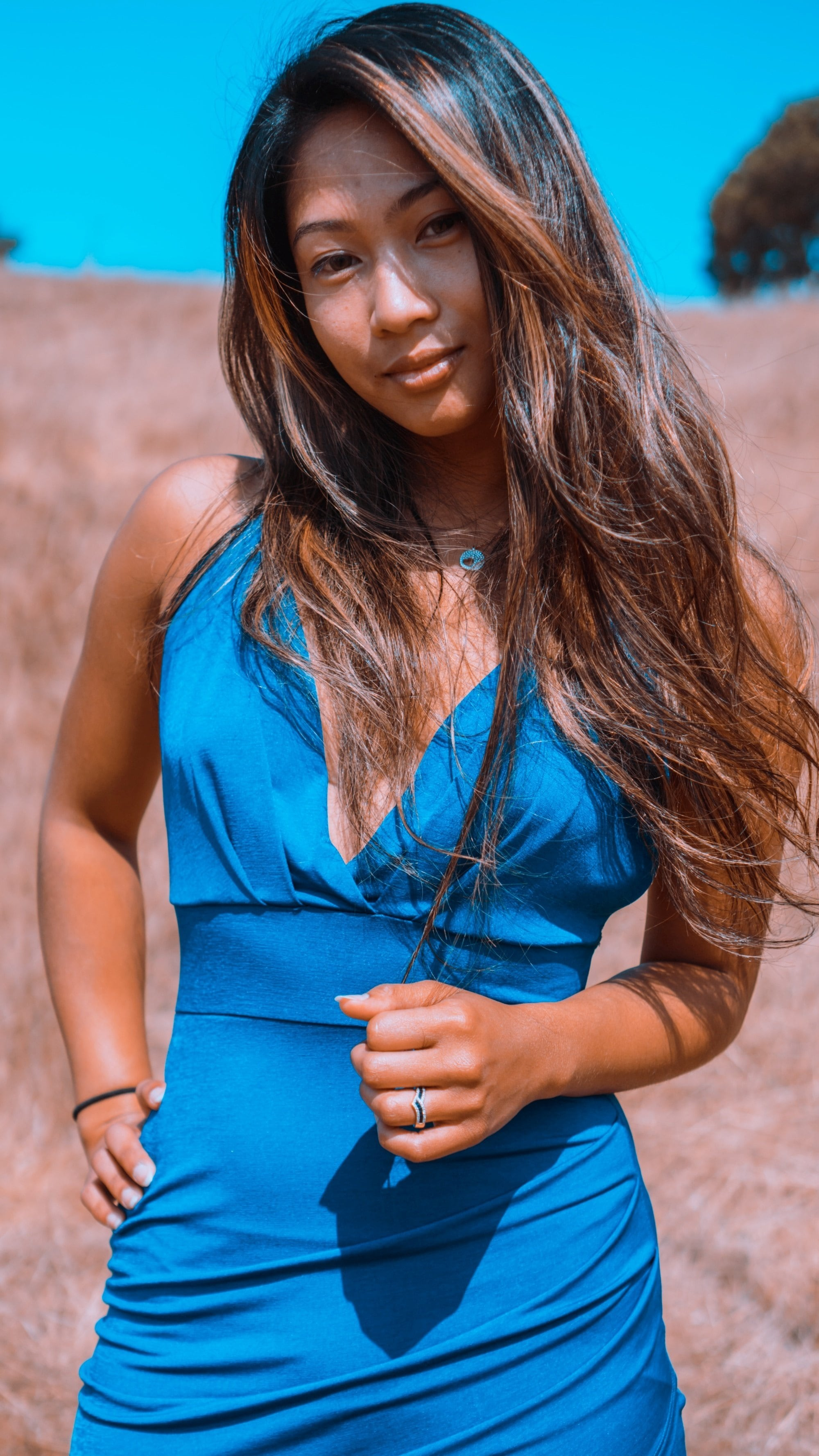 Asian woman with morena skin and long dark hair wearing a blue dress