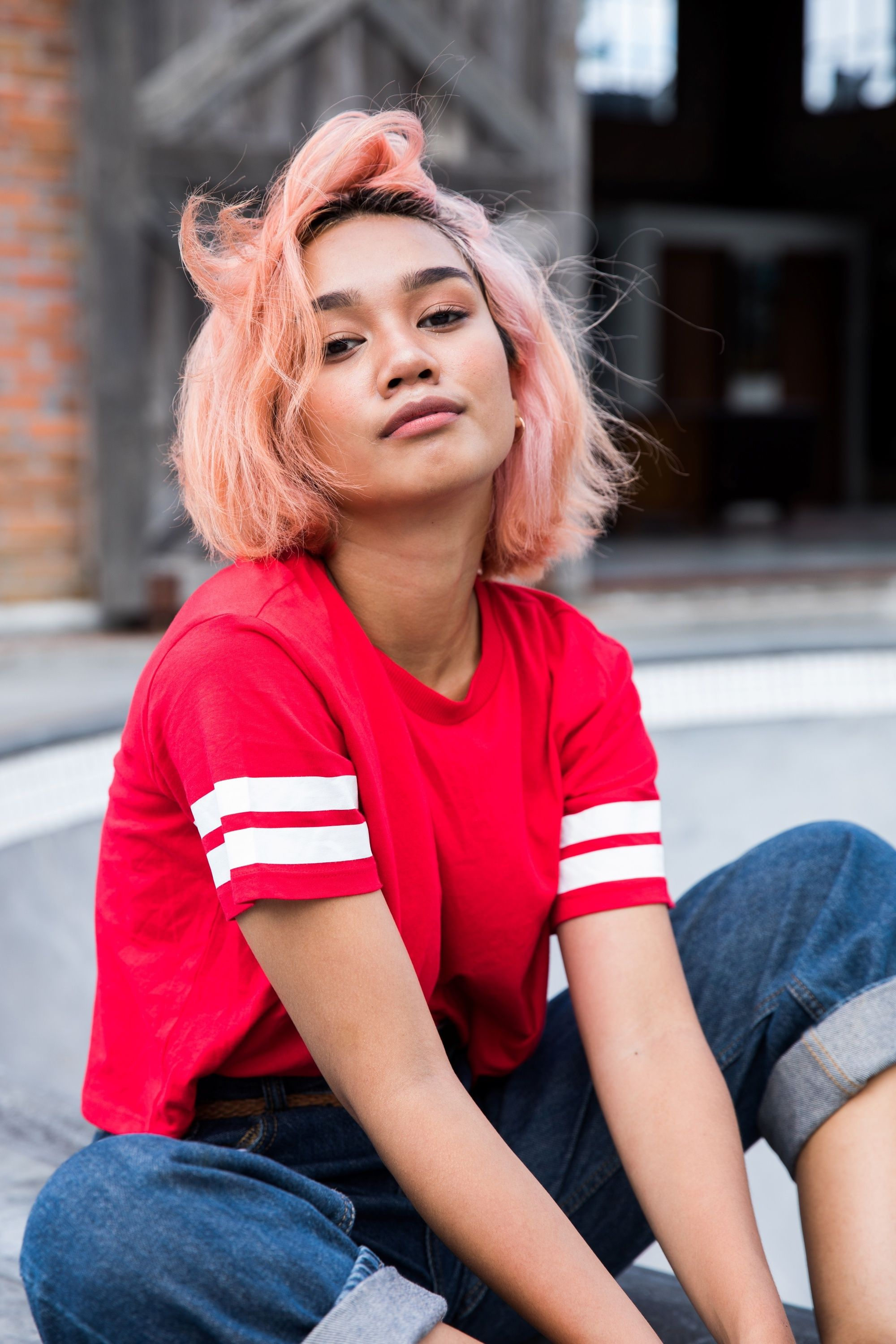 Asian woman with short light coral pink hair wearing a red shirt