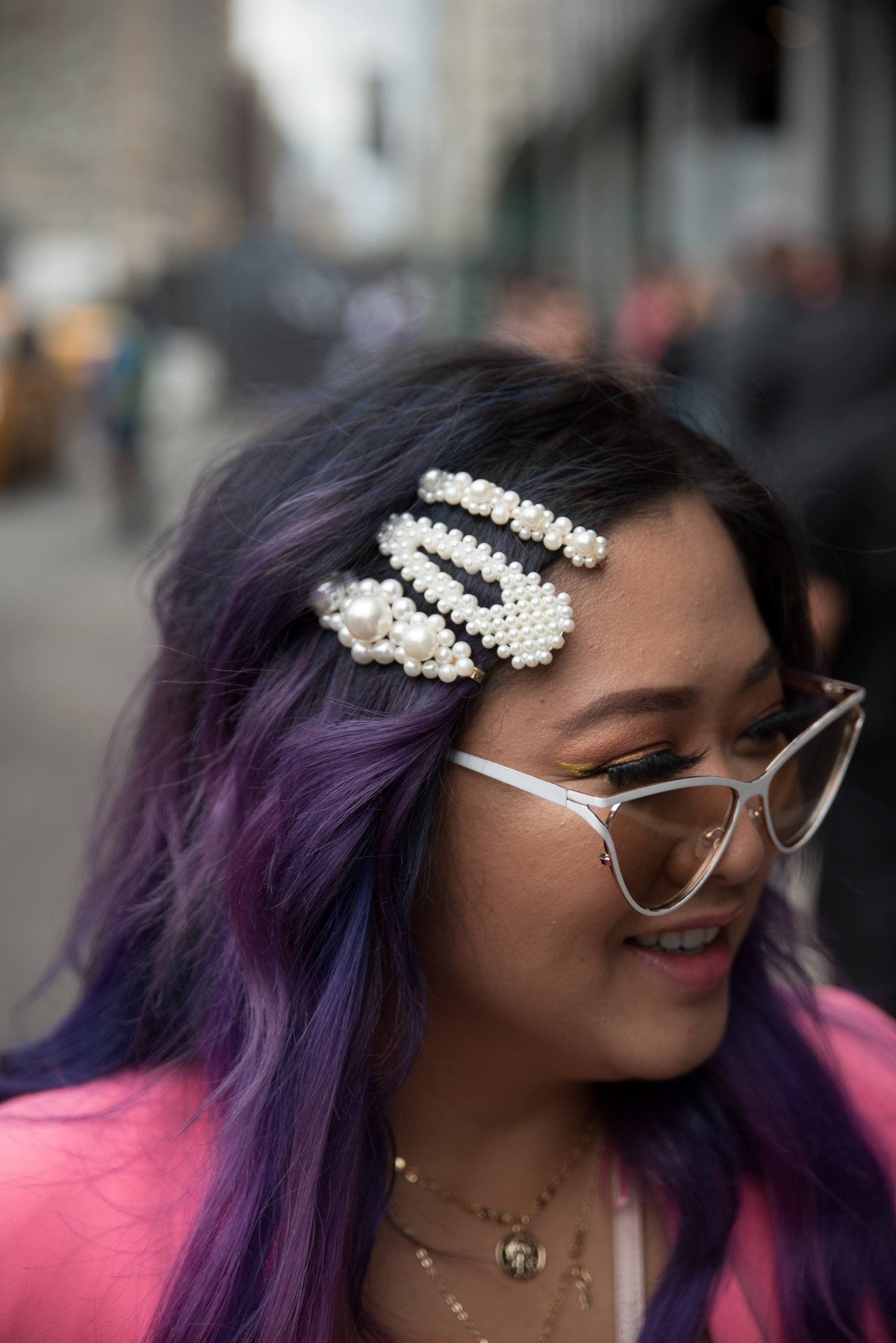 Asian woman with purple hair wearing white hair clips and sunglasses