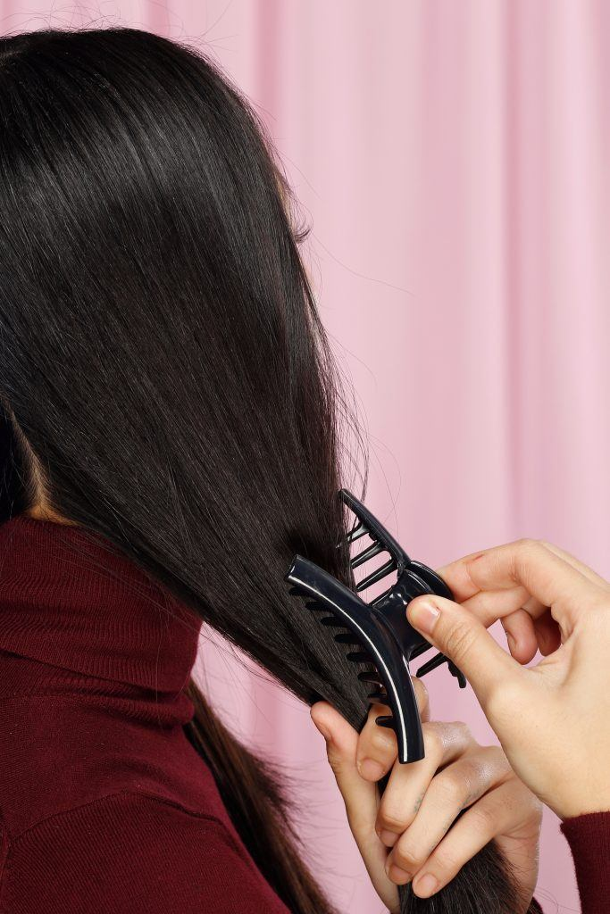 Closeup shot of an Asian woman clipping one side of her hair