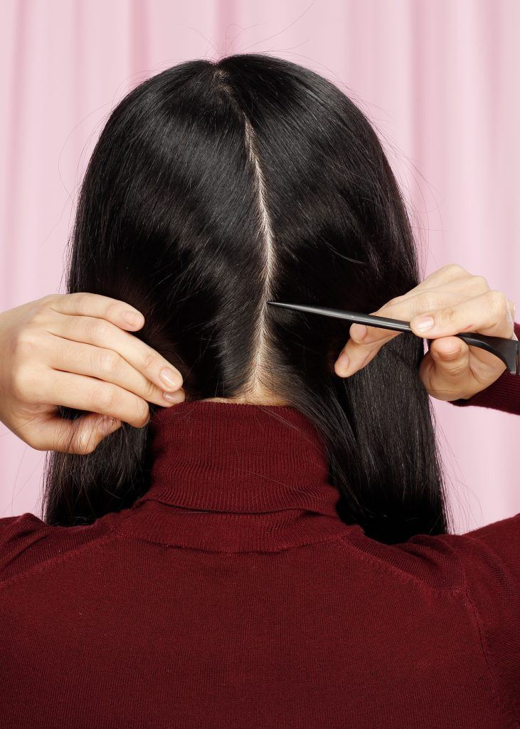 Back shot of an Asian woman parting her hair at the center