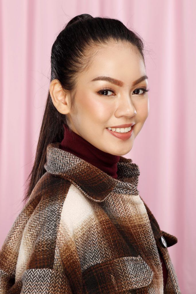 Asian woman with a high ponytail wearing a jacket