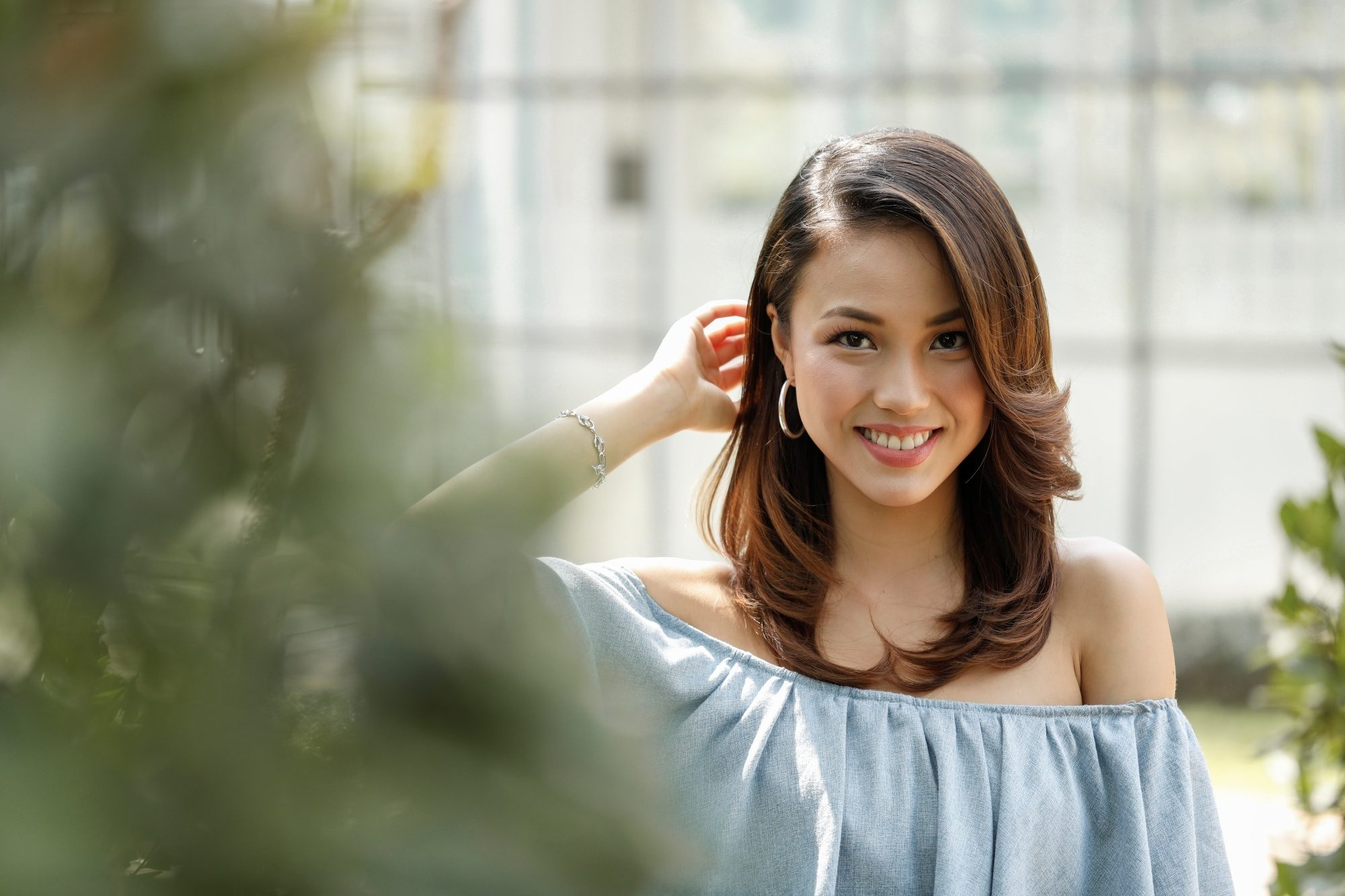 Asian woman with balayage brown hair wearing a blue off-shoulder top