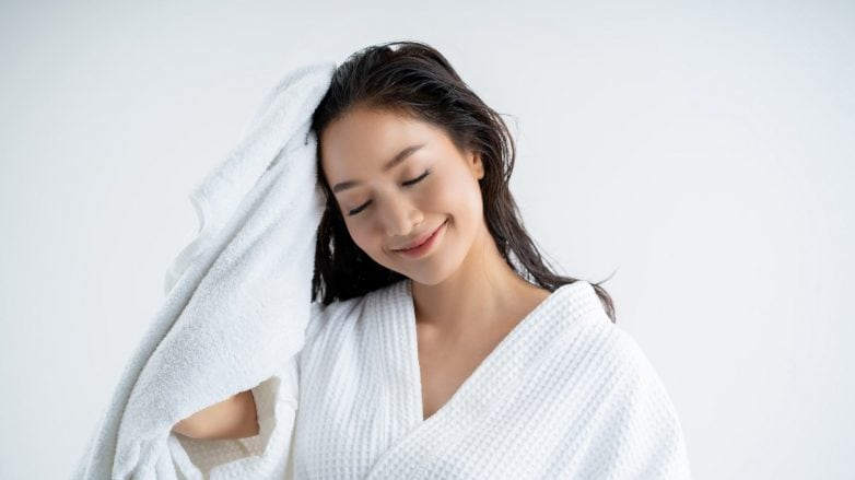 Asian woman wearing a white robe towel-drying her newly washed hair