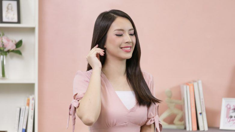How to apply hair mask: Asian woman with long hair wearing a pink top
