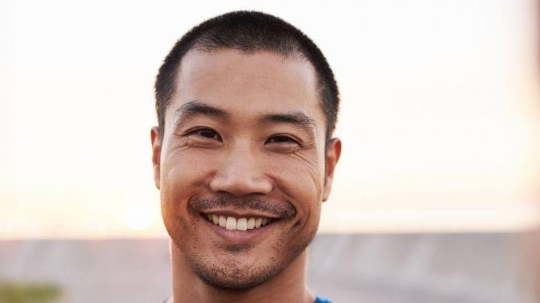 Asian man with a buzz cut wearing a blue shirt
