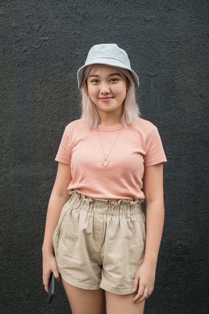 Asian woman with short platinum blonde hair and hat