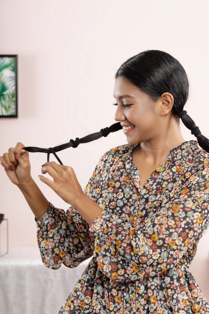 Asian woman putting hair ties on her long hair