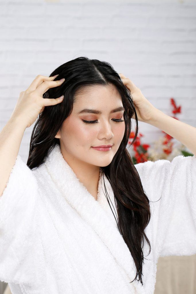 Asian woman applying coconut oil treatment to her long hair