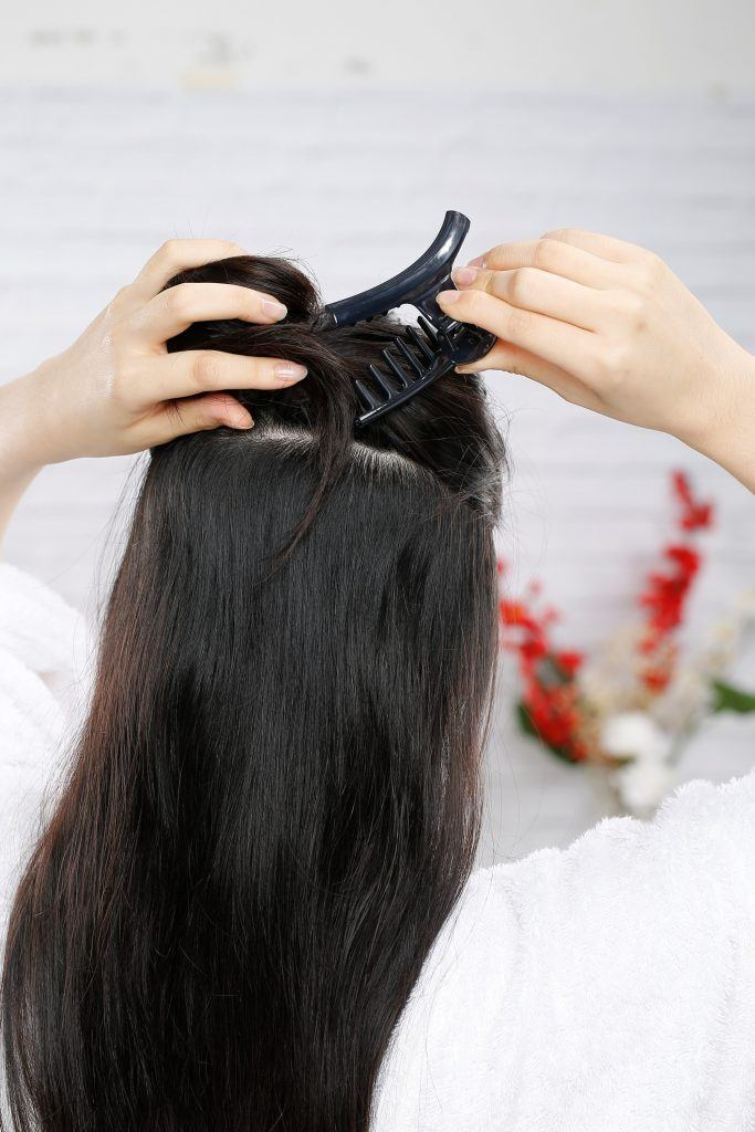 DIY Treatment for long hair: Back shot of Asian woman clipping a section of her hair