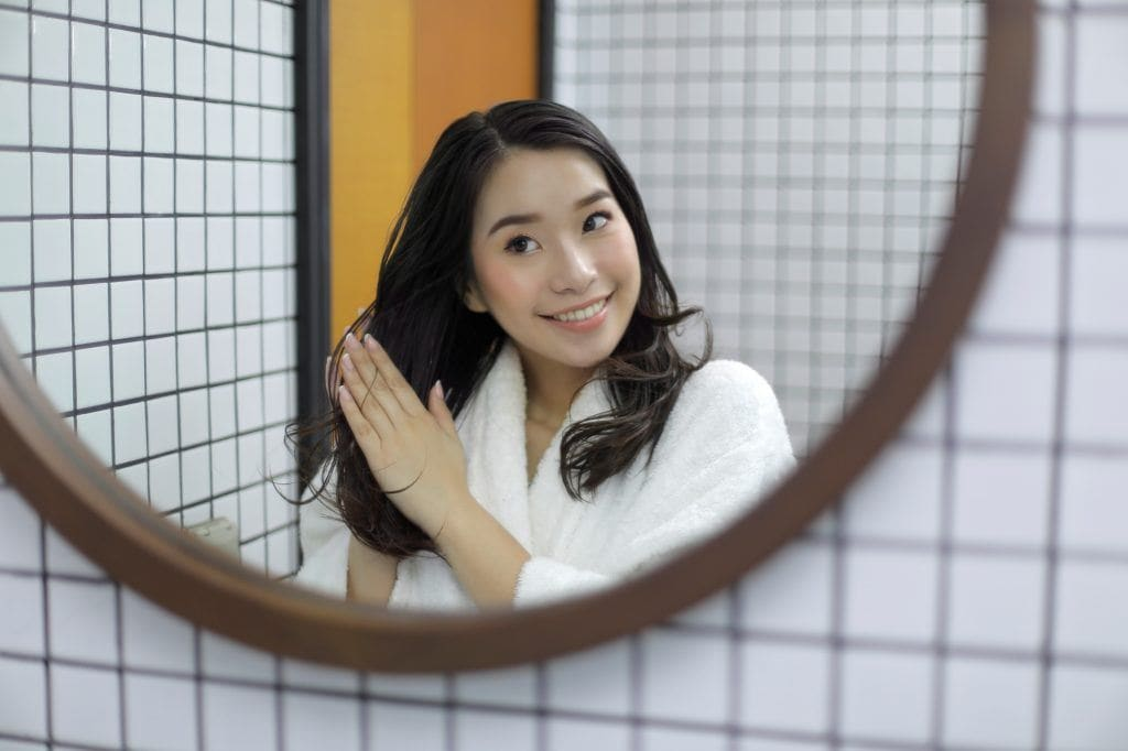 Asian woman facing the mirror applying oil to her hair