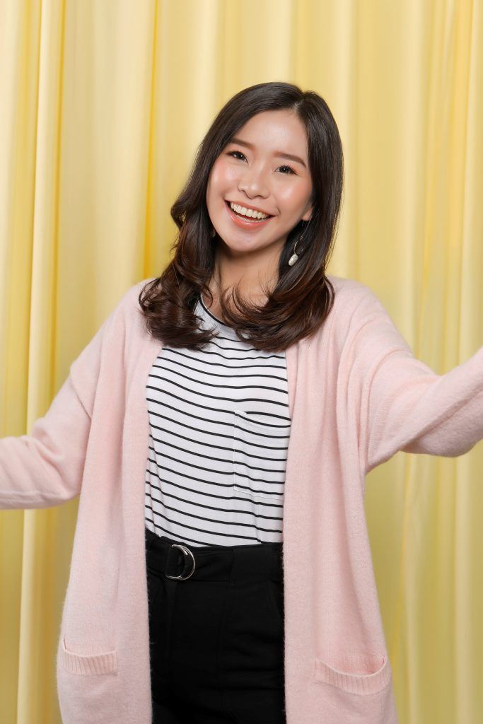 Asian woman wearing a pink cardigan miling