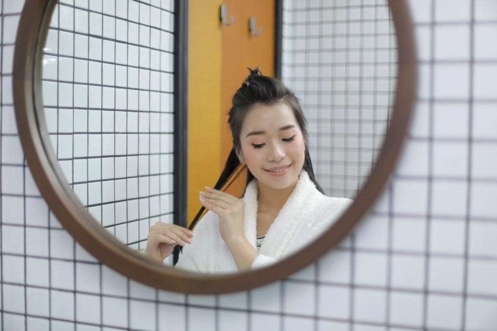 Asian woman applying DIY treatment to her hair