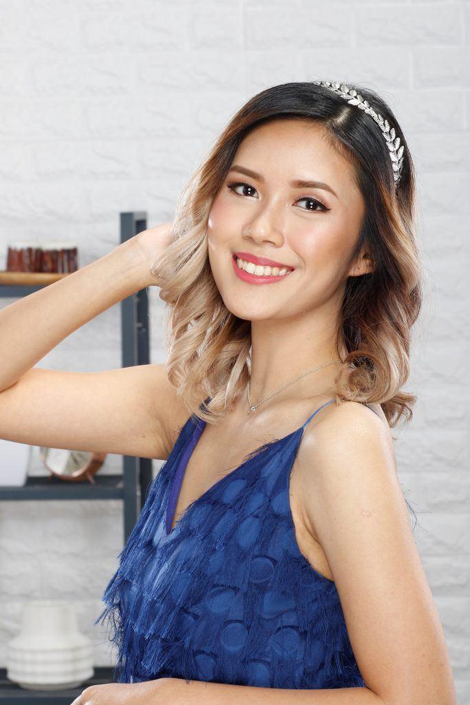 Asian woman with curly hair wearing a metallic headband