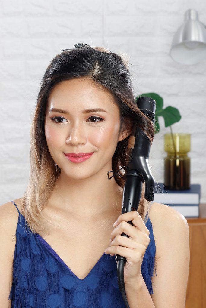 Asian woman curling a portion of her hair