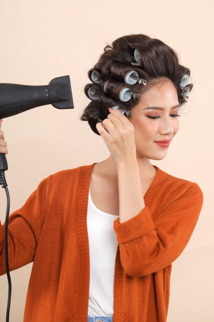 Asian woman blow drying her hair wrapped around hair rollers