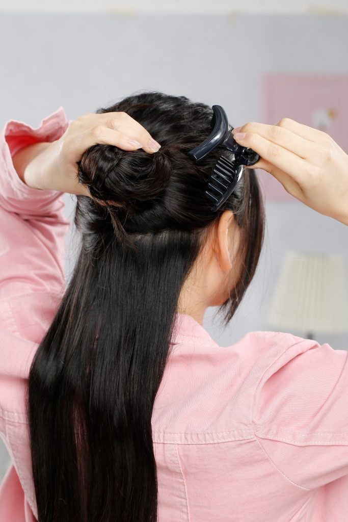 Back shot of an Asian woman using a claw clip