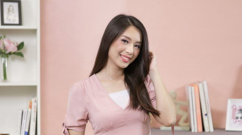 Amino Serum Conditioner: Asian woman with long hair wearing pink against a pink wall