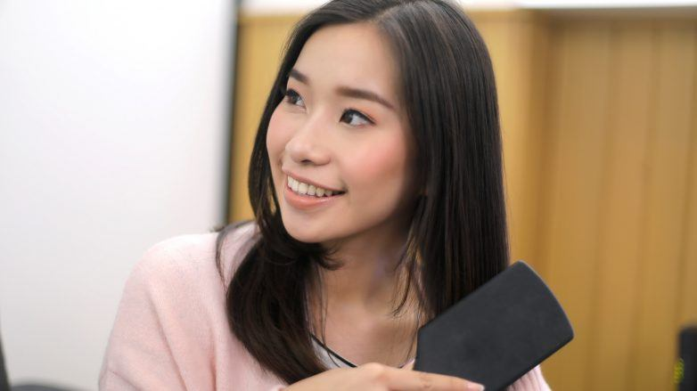 Asian woman brushing her hair and smiling