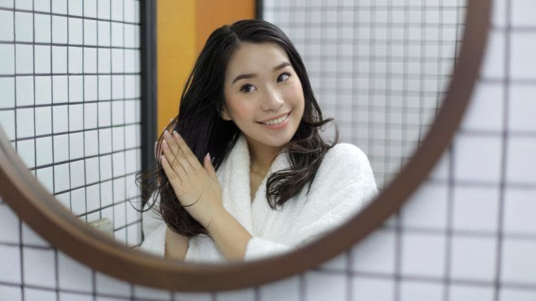 Asian woman applying hair treatment while looking in the mirror