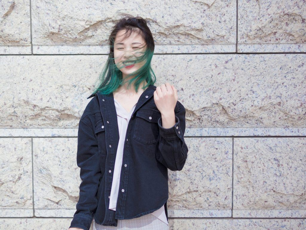 Asian woman with green hair smiling and wearing a denim jacket