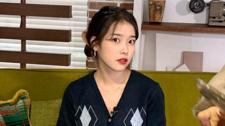 Iu short hair: Korean singer Iu sitting on a chair wearing a dark blue top