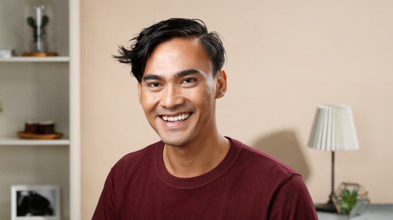 Men's hair: Asian man with short hair wearing a maroon shirt smiling