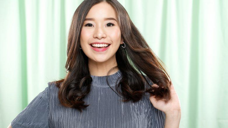 Hair fall treatment: Asian woman smiling and touching her long hair