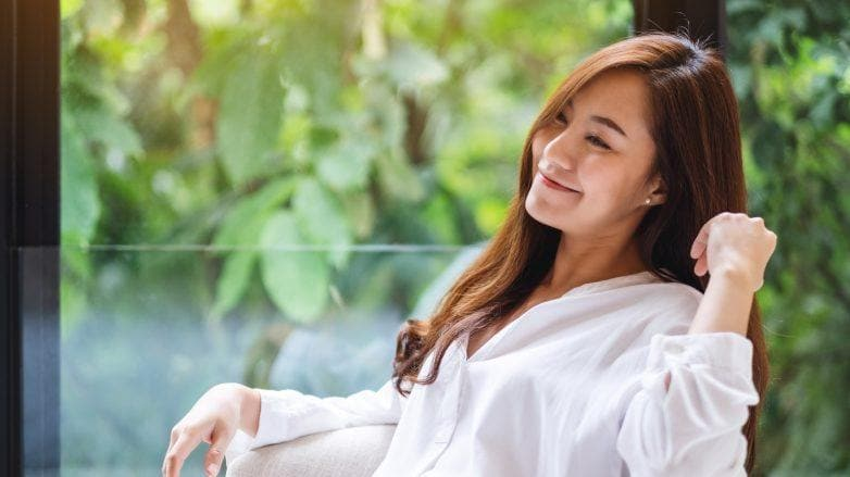 Dry scalp treatment: Asian woman sitting and touching her hair