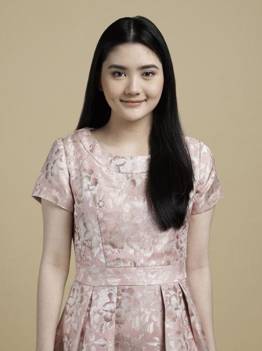 ผู้หญิงผมยาว เกล้าผมมวยต่ำ สวมชุดเดรสสีชมพูดูสวยหวาน