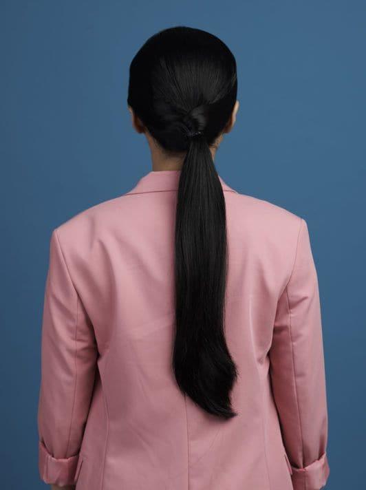 ผู้หญิงผมยาวสีดำ มัดผมหางม้า สวมสูทสีชมพู