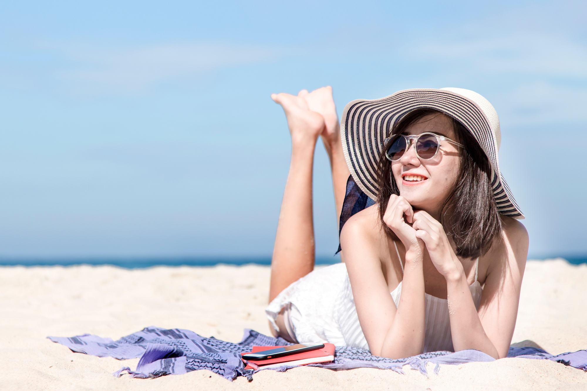 ผู้หญิงสวมหมวก แว่นตากันแดด ท่ามกลางแสงแดด