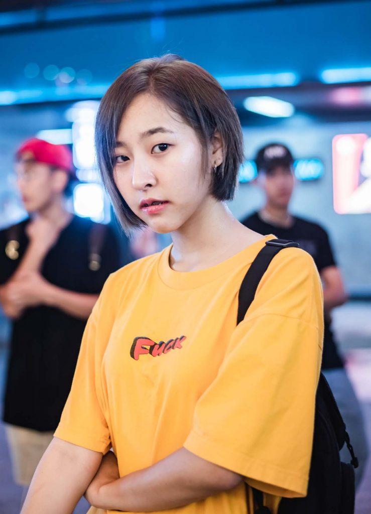 ผู้หญิงเอเชียผมสั้นตัดผมบ๊อบสั้น ใส่เสื้อสีเหลือง