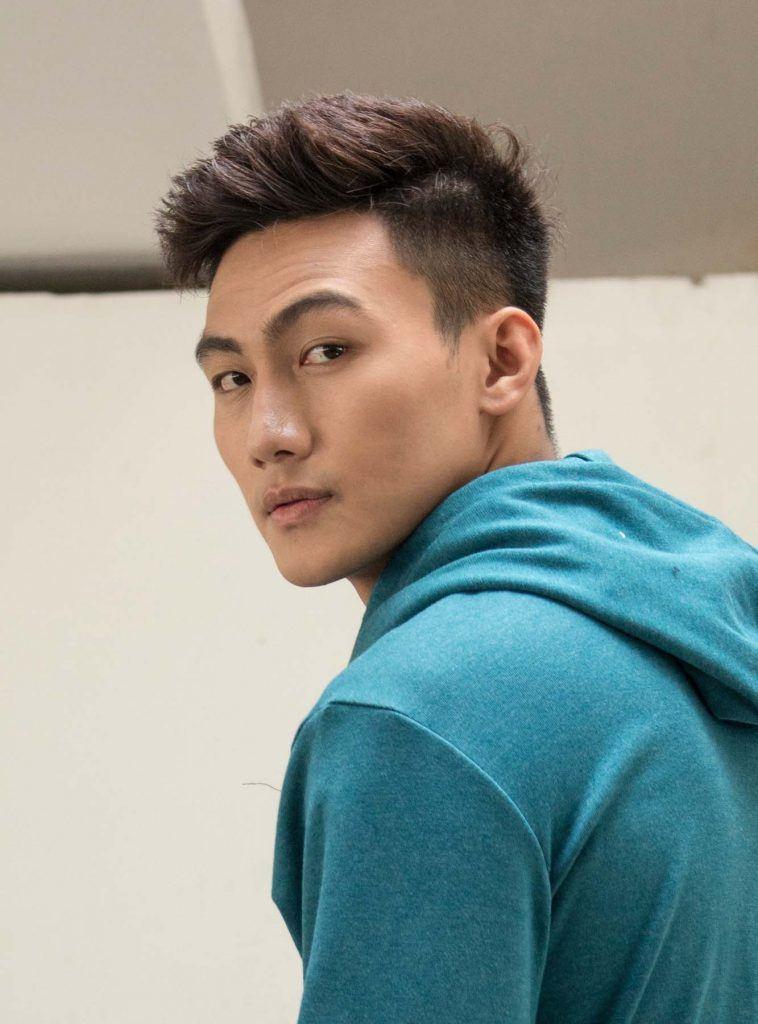 ผู้ชายไทยตัดผมสั้น ใส่เสื้อสีเขียว