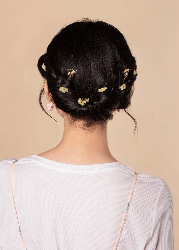 ผู้หญิงเอเชียผมสั้น ใส่เสื้อสีชมพูอ่อน ทำทรงผมเกล้าประดับด้วยดอกไม้ดอกเล็กๆ