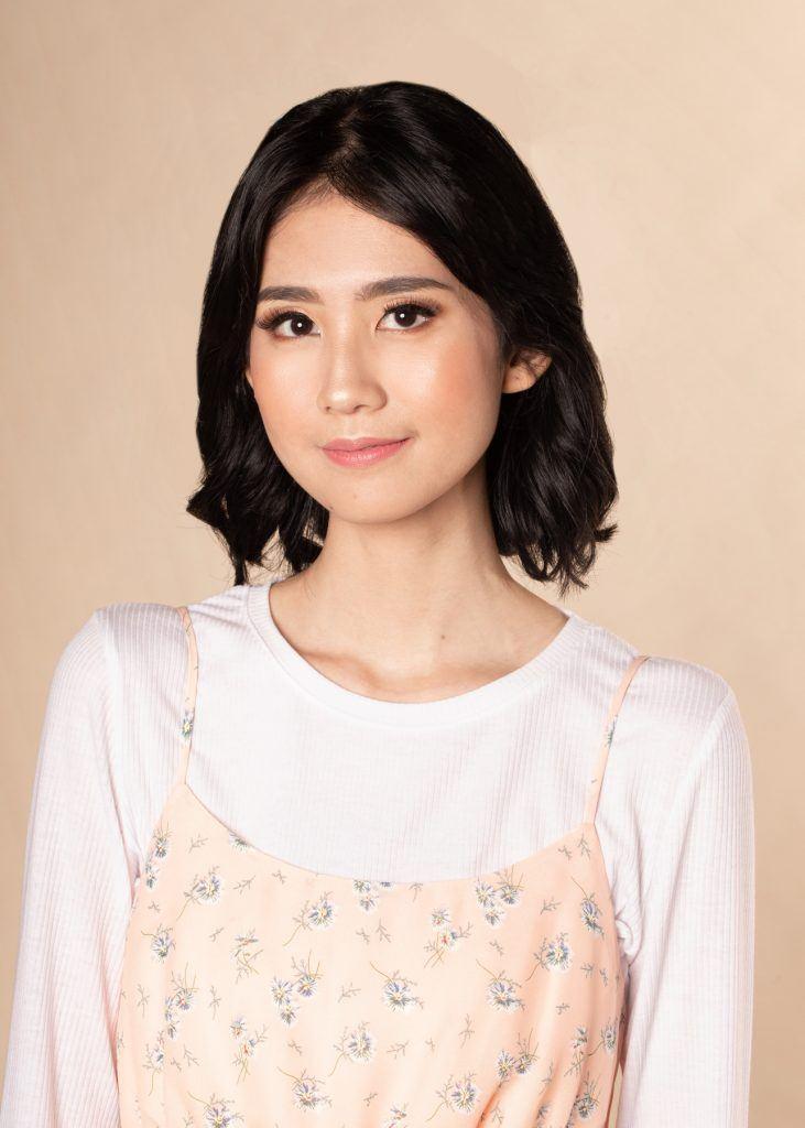 ผู้หญิงเอเชียผมสั้น ใส่เสื้อสีชมพูอ่อน