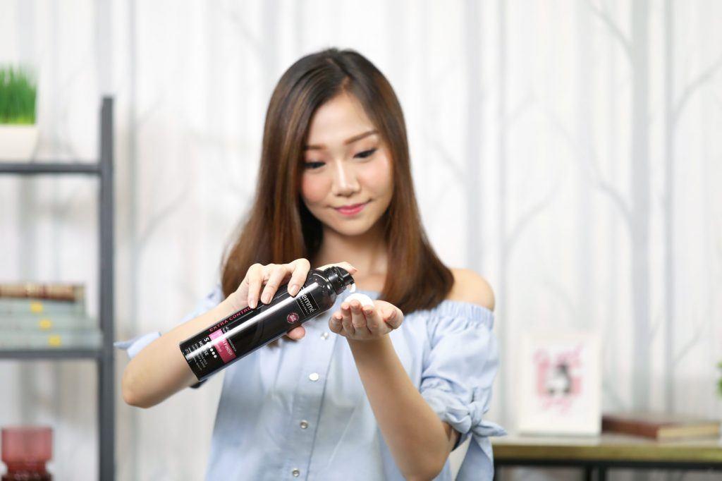 ผู้หญิงเอเชียผมยาวประบ่าสีดำ กำลังบีบมูสลงบนฝ่ามือ