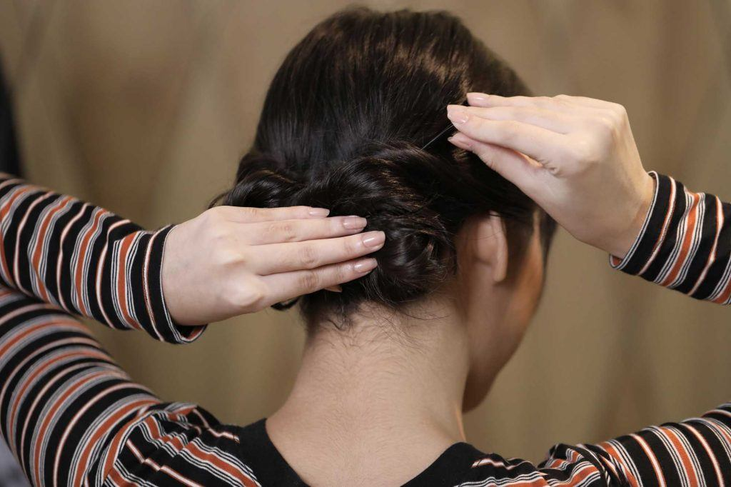 ผู้หญิงเอเชียผมประบ่าสีดำ กำลังทำผมมวยต่ำ