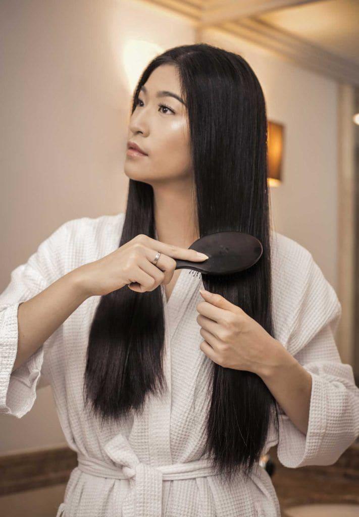 ผู้หญิงเอเชีย ผมยาว กำลังแปรงผม
