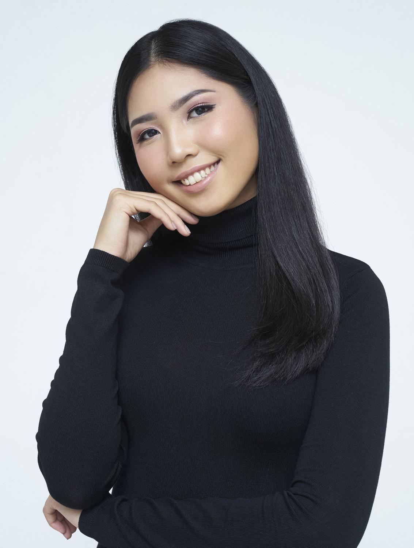 ผู้หญิงเอเชีย ผมยาว ใส่เสื้อสีดำคอเต้า ยืนเอามือเท้าคาง