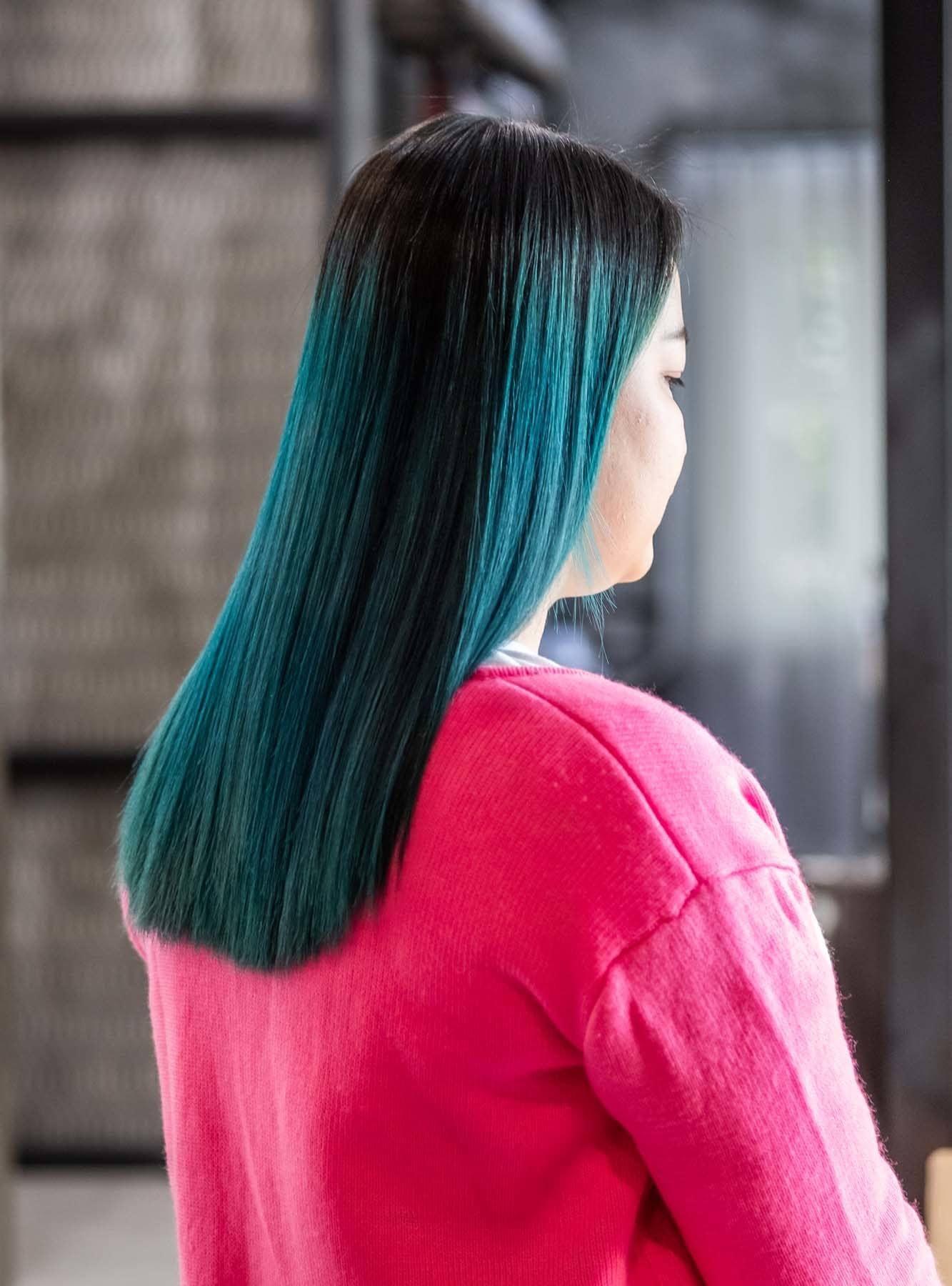 ผู้หญิงเอเชีย สวมเสื้อสีชมพู ผมสีเขียวน้ำทะเล