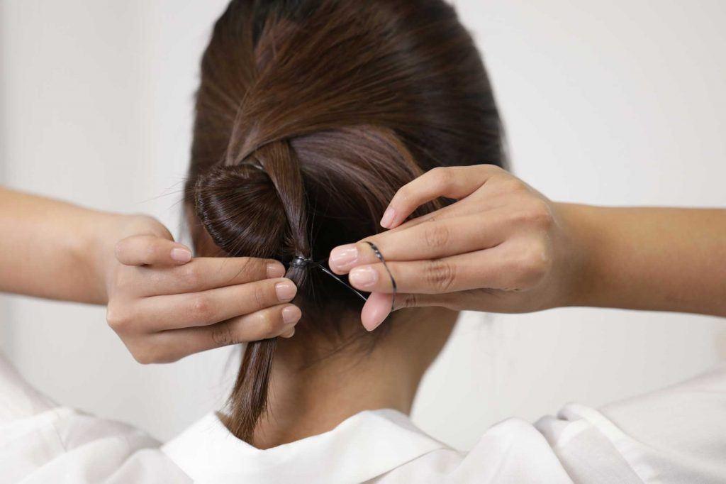 ผู้หญิงเอเชียผมยาวประบ่าสีดำ กำลังมัดผม