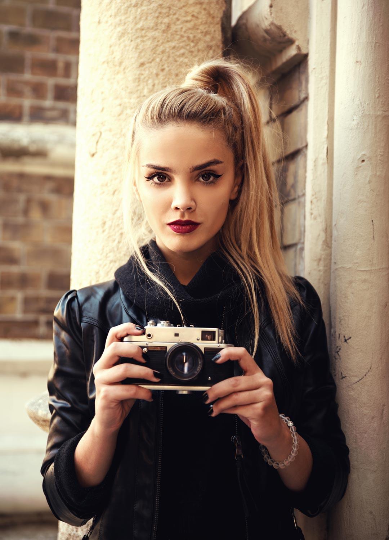 ผู้หญิง มัดผมหางม้าสูง ถือกล้องถ่ายรูป