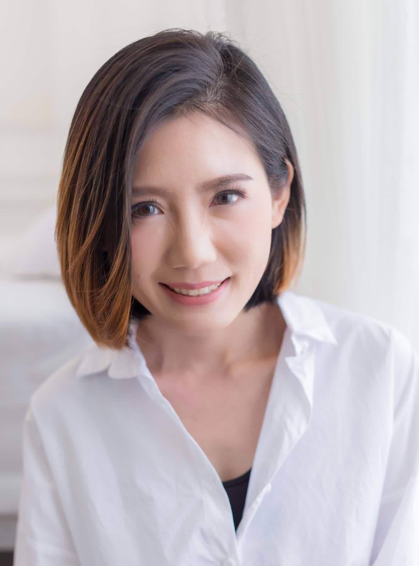 ผู้หญิงเอเชีย สวมเสื้อสีขาว ตัดผมบ๊อบสั้น