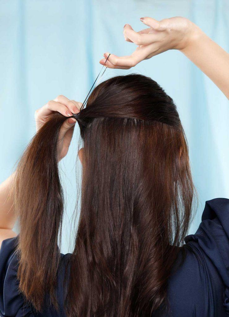 ผู้หญิงเอเชียผมยาวสีดำ กำลังมัดผมครึ่งหัว